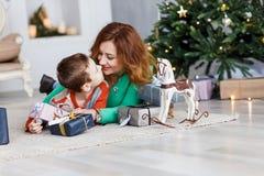 Мать и сын с подарками на рождество перед мех-деревом с свечами Стоковые Изображения