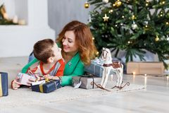 Мать и сын с подарками на рождество перед мех-деревом с свечами Стоковая Фотография