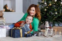 Мать и сын с подарками на рождество перед мех-деревом с свечами Стоковые Фото