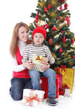 Мать и сын с подарками под рождественской елкой стоковые изображения