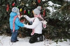 Мать и сын украшают рождественскую елку внешнюю в парке зимы Подарки и рождественские елки Стоковое Изображение RF