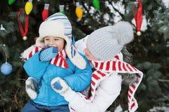 Мать и сын украшают рождественскую елку внешнюю в парке зимы Подарки и рождественские елки Стоковые Изображения