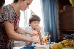 Мать к кашевару сына торт с свечами Стоковая Фотография RF