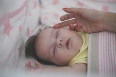 Мать ласкает ее маленького младенца стоковая фотография
