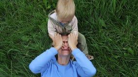 Мать лежа на траве около усаживания сына и смеяться с ним Ребенок закрывает маму глаз рук, прятк игры видеоматериал