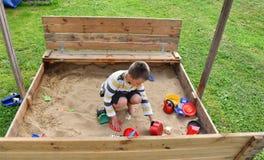 Мать мальчика ребенка семьи играя в sandpit в лете Стоковое Изображение RF