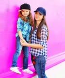 Мать моды и маленькая девочка ребенка в checkered рубашках и бейсбольных кепках в городе на красочной розовой стене стоковые фотографии rf