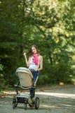 Мать нажимая детскую дорожную коляску в парке Стоковые Изображения