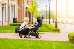 Мать носит ее ребенка в прогулочной коляске для прогулки стоковое изображение
