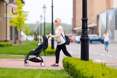 Мать носит ее ребенка в прогулочной коляске для прогулки стоковое фото rf