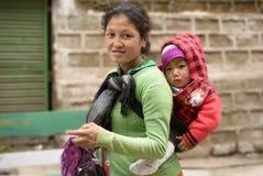 Мать нося ее меньшего ребенка на ей назад для работы стоковое изображение rf