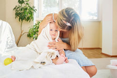Мать обнимает ее младенца в комнате полотенца внутри комнаты стоковые изображения