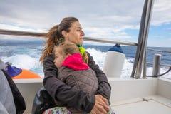 Мать обнимая ее дочь в плавании моторки в океане стоковая фотография rf