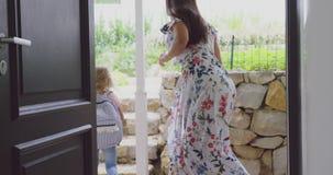 Мать обнимая ее дочь перед покидать школа на дверь в домашнее 4k сток-видео