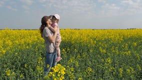 Мать обнимая ее дочь в природе Женщина с маленькой девочкой на желтом поле семья счастливая сток-видео