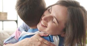 Мать обнимая ее сына дома видеоматериал