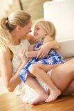 Мать ослабляя дома с дочью Стоковые Изображения RF
