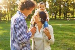 Мать, отец и дочь идут в парк стоковое фото rf