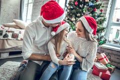 Мать, отец и дочь с взглядом привлекательного возникновения на друг друга глазах, сидят на белом ковре около украшенного дерева Н стоковая фотография rf