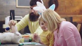 Мать, отец и сын красят яичка Счастливая семья подготавливает для пасхи Зайчик милого мальчика маленького ребенка нося видеоматериал