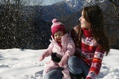 мать дочи играя снежок Стоковые Изображения