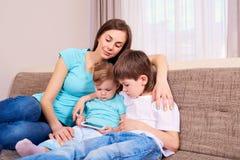 Мать, дочь, сын, внутри помещения играя с телефоном Стоковые Изображения RF