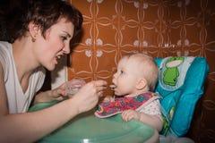 Мать подает пюре младенца младенца Стоковые Изображения RF