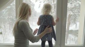 Мать показывает ландшафт зимы к ее маленькой дочери через окно сток-видео