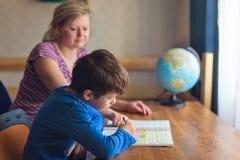 Мать помогает сыну разрешая домашнюю работу математики на столе Стоковое Изображение RF