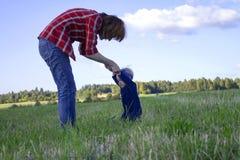 Мать помогая ее маленькой дочери стоять вверх Стоковые Фото