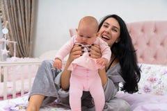 Мать помогая ее младенцу стоять стоковая фотография