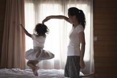 Мать портрета и ее дочь играя на спальне стоковое фото