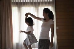 Мать портрета и ее дочь играя на спальне стоковая фотография