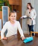 Мать порции девушки для того чтобы очистить квартиру Стоковое Изображение