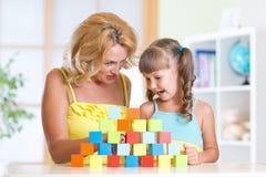 Мать постаретая серединой помогая ее preschooler Стоковое Фото