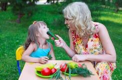 Мать подавая ее ребенк с огурцом Стоковое фото RF