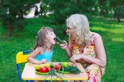 Мать подавая ее ребенк с огурцом Стоковые Фото