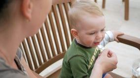 Мать подает ее молодой сын с мороженым от ложки Они сидят в кафе улицы Мальчик действительно любит видеоматериал