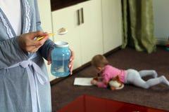 Мать подготавливая молоко для вашего ребенка младенец на предпосылке горизонтально Стоковая Фотография RF