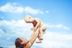 Мать поднимает ребенка стоковое изображение rf