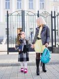Мать принимает ее дочь от школы, семьи концепции стоковые изображения