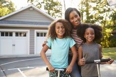 Мать при дети ехать самокаты на подъездной дороге дома стоковые изображения
