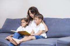 Мать при 2 дет читая книгу совместно Стоковые Изображения