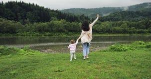 Мать при дочь бежать к рукам реки и владения счастливые моменты материнства Предпосылка гор Ветрянка дальше видеоматериал