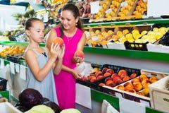 Мать при девушка принимая персики на рынке стоковое фото