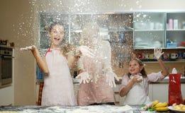 Мать при ее 2 дет имея потеху в кухне Стоковые Изображения RF