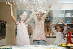Мать при ее 2 дет имея потеху в кухне Стоковая Фотография