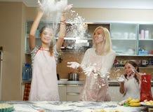 Мать при ее 2 дет имея потеху в кухне Стоковые Изображения