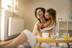 Мать при ее маленькая дочь имея завтрак в кровати стоковые фотографии rf