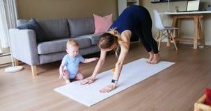 Мать при ее младенец выполняя йогу 4k акции видеоматериалы